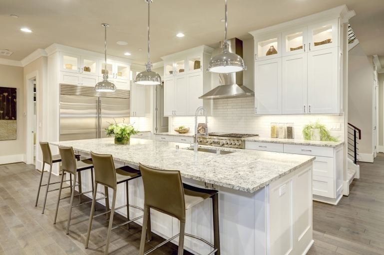 White kitchen design features large bar style kitchen island with granite countertop illuminated by modern pendant lights. Stainless steel appliances framed by white shaker cabinets . Northwest, USA
